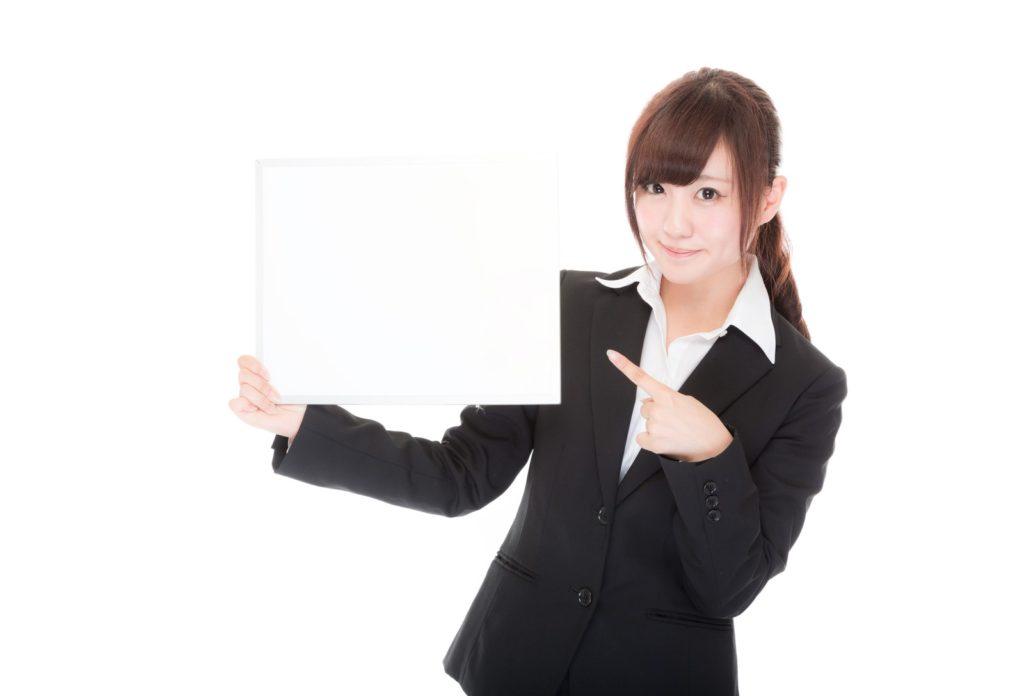 ホワイトボードを持つスーツの女性