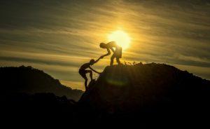 登山で助け合う人